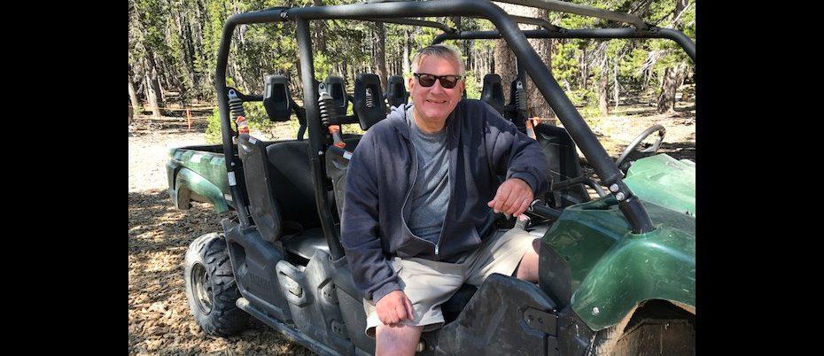 Greg sitting in ATV in woods